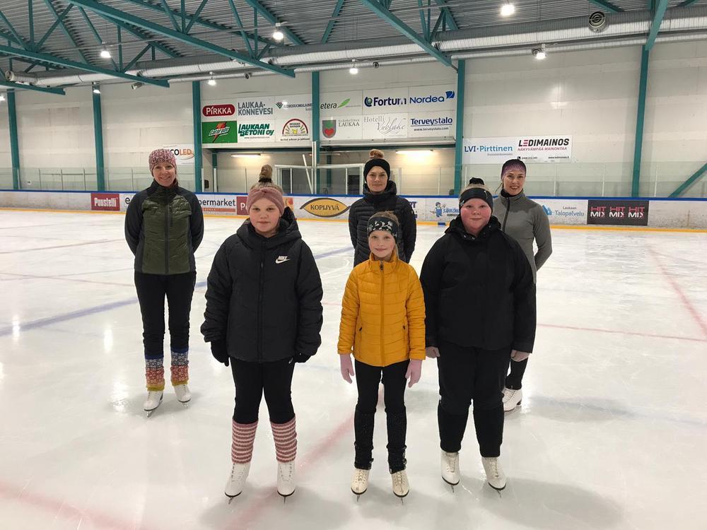 Kolme aikuista ja kolme lasta luistimille jäällä, Peurungan jäähallissa.